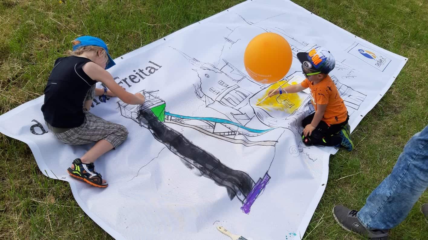 Kinder malen die Plane von RundumFit Freital aus